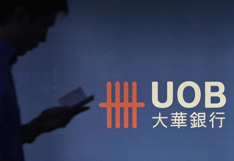 A man passes a logo of United Overseas Bank in the central business district in Singapore