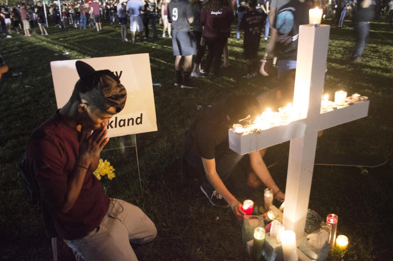 Jay Eaton, 19, prays for the lives lost in this week's school shooting. He said he's thankful his cousins, who attend Stoneman Douglas High, weren't killed. (Johanne Rahaman for HuffPost)