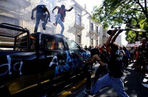 Demonstrators attack a police vehicle during a protest in Guadalajara (AFP via Getty Images)