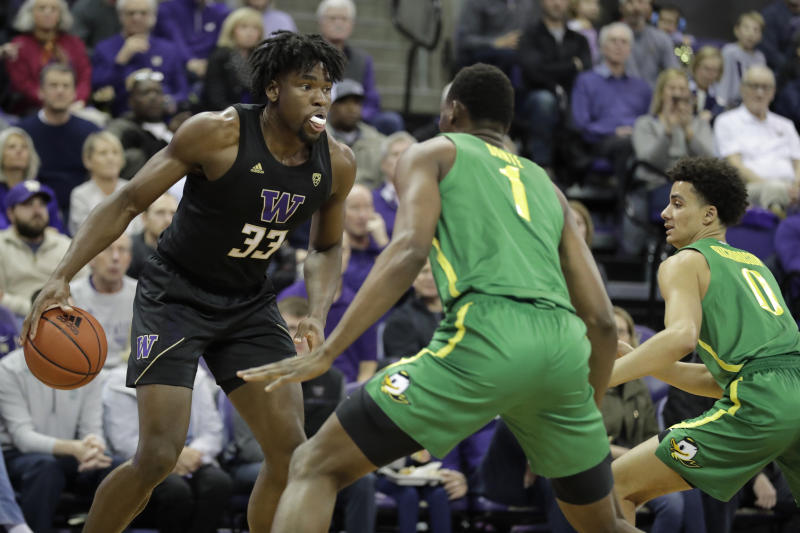 Washington forward Isaiah Stewart (33) looks to pass against Oregon center N'Faly Dante (1) and guard Will Richardson, right, during the first half of an NCAA college basketball game, Saturday, Jan. 18, 2020, in Seattle. (AP Photo/Ted S. Warren)