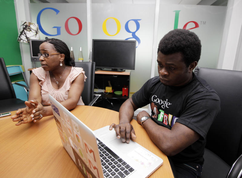 In this photo taken, Thursday, Sept.13, 2012, Affiong Osuchukwu, Google's Nigeria marketing manager, left, with unidentified man speaks to the Associated Press, during an interview, in Lagos, Nigeria. With all its cutting-edge technology, Google Inc. has turned back to the text message in its efforts to break into Nigeria's booming economy. The search engine has started a service in Nigeria, as well as Ghana and Kenya, allowing mobile phone users to access emails through text messaging. That comes as the company's office in Lagos has begun working with small business owners in this nation of more than 160 million people. (AP Photo/Sunday Alamba)