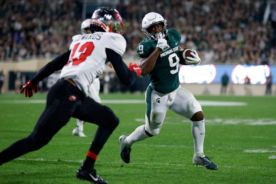Michigan State's Kenneth Walker III, right, runs for a touchdown against Western Kentucky's Miguel Edwards during the first quarter of an NCAA college football game, Saturday, Oct. 2, 2021, in East Lansing, Mich.