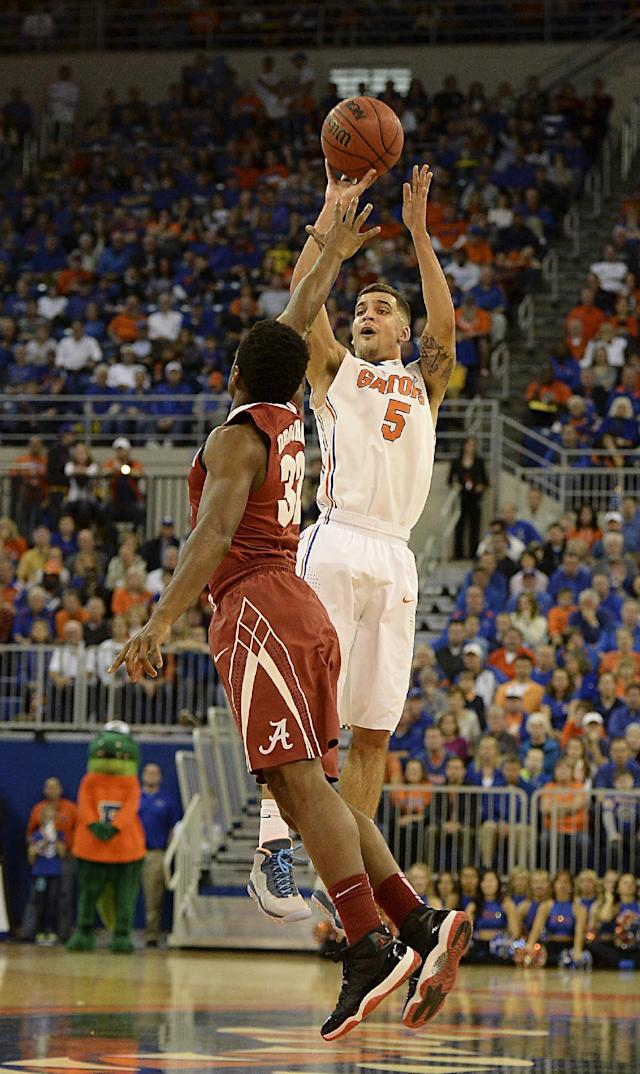Florida guard Scottie Wilbekin (5) goes for 3-points over Alabama guard Retin Obasohan (32) during the first half of an NCAA college basketball game Saturday, Feb. 8, 2014, in Gainesville, Fla. Wilbekin scored 16 points in Florida's 78-69 win. (AP Photo/Phil Sandlin)