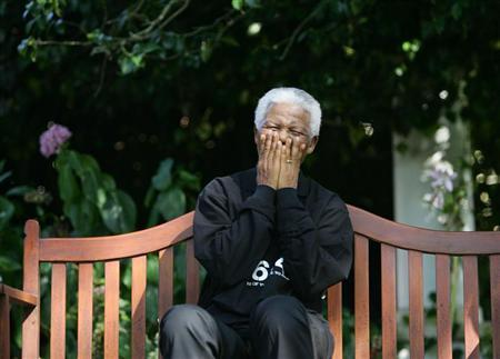Nelson Mandela laughs with journalists and performers participating in the second 46664 ...