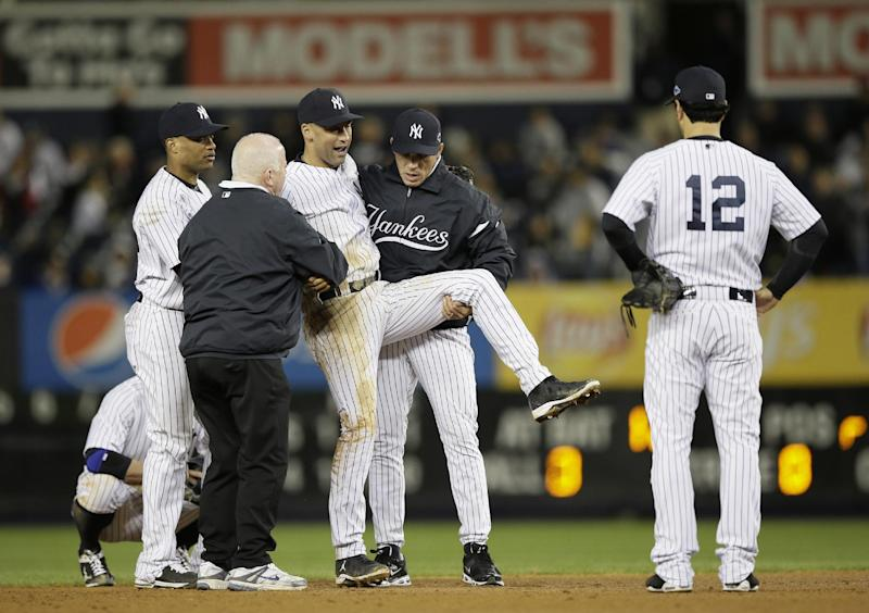 Trainer Steve Donohue, second from left, and New York Yankees manager Joe Girardi, second from right, help Derek Jeter off the field after he injured himself during Game 1 of the American League championship series against the Detroit Tigers Sunday, Oct. 14, 2012, in New York. New York Yankees' Robinson Cano, left, and Eric Chavez stood by.  (AP Photo/Matt Slocum)