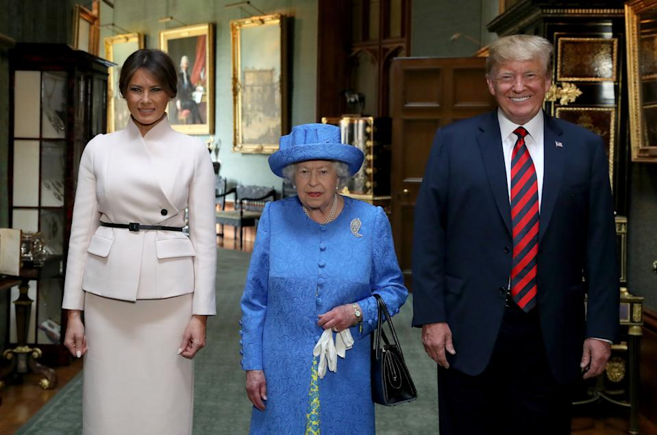 """Britain's Queen Elizabeth II (C) stands with US President Donald Trump (R) and US First Lady Melania Trump (L) in the Grand Corridor at Windsor Castle in Windsor, west of London, on July 13, 2018 during an engagement on the second day of Trump's UK visit. - US President Donald Trump launched an extraordinary attack on Prime Minister Theresa May's Brexit strategy, plunging the transatlantic """"special relationship"""" to a new low as they prepared to meet Friday on the second day of his tumultuous trip to Britain. (Photo by Steve Parsons / POOL / AFP) (Photo by STEVE PARSONS/POOL/AFP via Getty Images)"""
