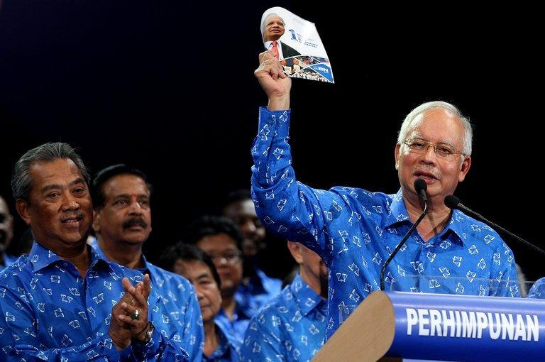 Malaysian Prime Minister Najib Razak (right) holds a manifesto at a rally in a suburb of Kuala Lumpur on April 6, 2013