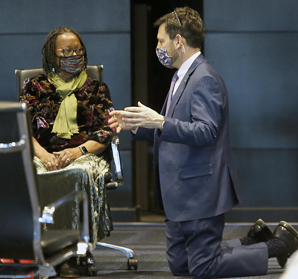 Sen. Scott Surovell, D-Fairfax, right, gets on his knees for a conversation with Sen. Mamie Locke, D-Hampton, who is chair of the Senate Democratic caucus, during the floor session of the Virginia Senate inside the Science Museum in Richmond, Va Thursday, Jan. 28, 2021. Surovell was talking with many of the members as the Senate met, trying to gain support for SB1165, his legislation eliminating the death penalty. He asked that the bill be brought up tomorrow. (Bob Brown/Richmond Times-Dispatch via AP)