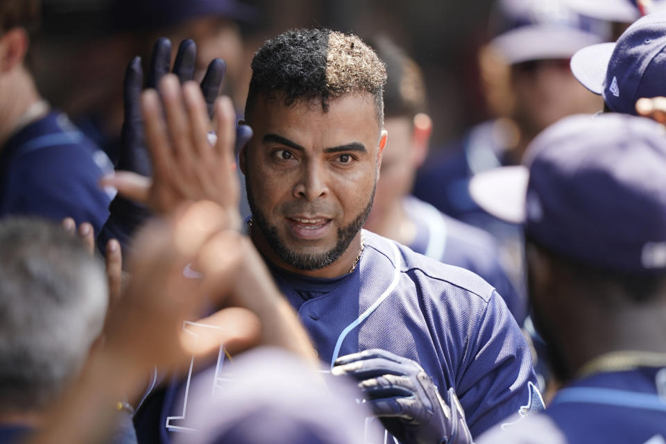 Tampa Bay Rays' Nelson Cruz is congratulated by teammates after hitting a solo home run in the sixth inning of a baseball game against the Cleveland Indians, Sunday, July 25, 2021, in Cleveland. (AP Photo/Tony Dejak)