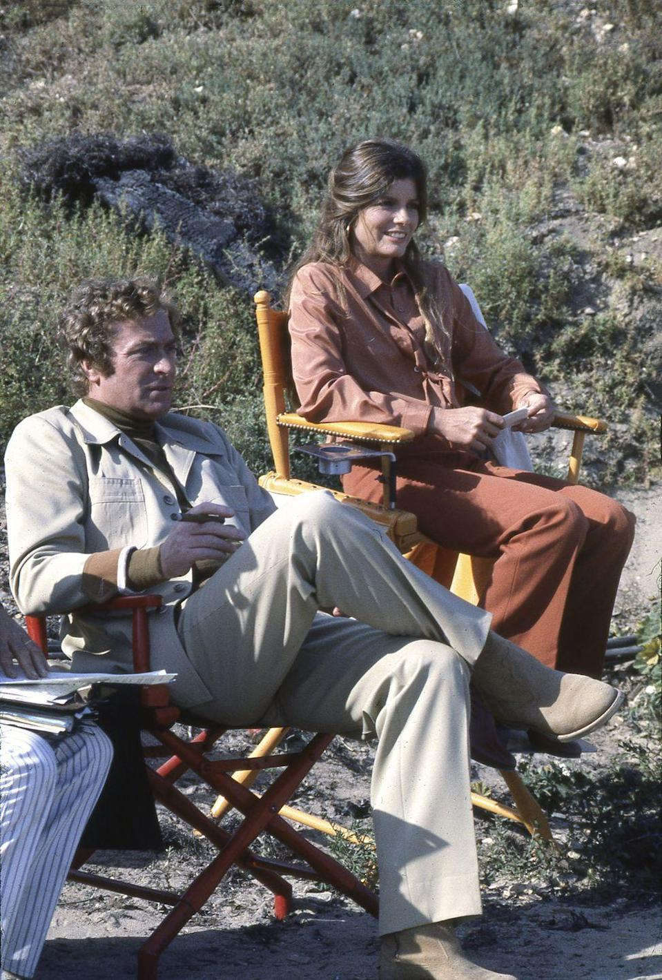 <p>Actress Katharine Ross sits on the sidelines with costar Michael Caine as they film the disaster movie <em>The Swarm</em> on location in 1977. </p>