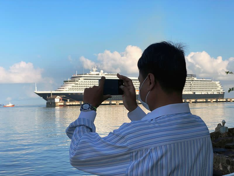 Man uses a phone to take a picture in front of the cruise ship MS Westerdam at dock in the Cambodian port of Sihanoukville