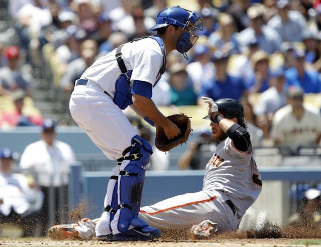 San Francisco Giants' Brandon Crawford, right, slides into home to beat the throw to Los Angeles Dodgers catcher Drew Butera, left, to score on a sacrifice fly hit by Giants' Hunter Pence in the second inning of a baseball game on Saturday, May 10, 2014, in Los Angeles. (AP Photo/Alex Gallardo)