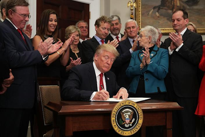 President Donald Trump signs an executive order to loosen restrictions on the Affordable Care Act in 2017.