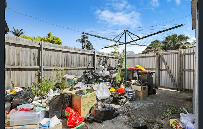 The rear courtyard of the Newtown property with rubbish piled up.