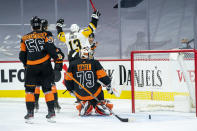 Pittsburgh Penguins' Brandon Tanev, center, reacts to his goal on Philadelphia Flyers goaltender Carter Hart, right, during the first period of an NHL hockey game, Friday, Jan. 15, 2021, in Philadelphia. (AP Photo/Chris Szagola)