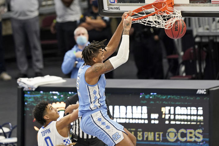 North Carolina's Armando Bacot (5) dunks the ball over Kentucky's Jacob Toppin (0) in the second half of an NCAA college basketball game, Saturday, Dec. 19, 2020, in Cleveland. North Carolina won 75-63. (AP Photo/Tony Dejak)