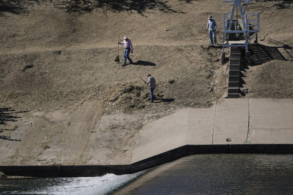 """Men in Ciudad Acuna, Mexico, are seen from Del Rio, Texas, as they clean up an area on near a dam along the Rio Grande, where migrants, many from Haiti, had been crossing, Thursday, Sept. 23, 2021, in Del Rio, Texas. The """"amistad,"""" or friendship, that Del Rio, Texas, and Ciudad Acuña, Mexico, celebrate with a festival each year has been important in helping them deal with the challenges from a migrant camp that shut down the border bridge between the two communities for more than a week. Federal officials announced the border crossing would reopen to passenger traffic late Saturday afternoon and to cargo traffic on Monday. (AP Photo/Julio Cortez)"""