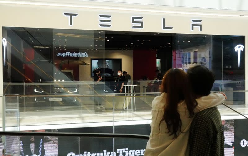 A couple looks at a Tesla dealership in Hanam