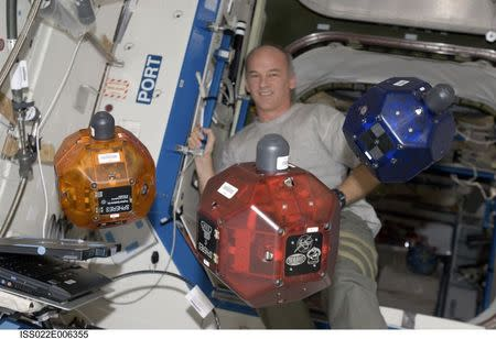 NASA astronaut Jeffrey Williams, Expedition 22 commander, performs a check of the Synchronized Position Hold, Engage, Reorient, Experimental Satellites (SPHERES) Beacon / Beacon Tester in the Destiny laboratory of the International Space Station in this December 5, 2009 NASA handout photo released to Reuters July 3, 2014. REUTERS/NASA/Handout via Reuters