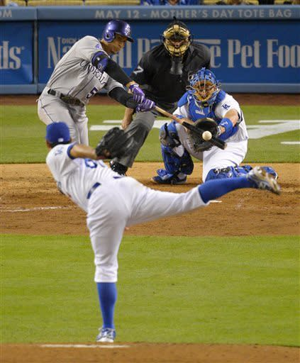 Colorado Rockies' Carlos Gonzalez, upper left, hits an RBI double as Los Angeles Dodgers starting pitcher Josh Beckett, lower left, pitches and catcher A.J. Ellis, right, catches while home plate umpire Larry Vanover looks on during the fourth inning of their baseball game against the Los Angeles Dodgers, Wednesday, May 1, 2013, in Los Angeles. (AP Photo/Mark J. Terrill)