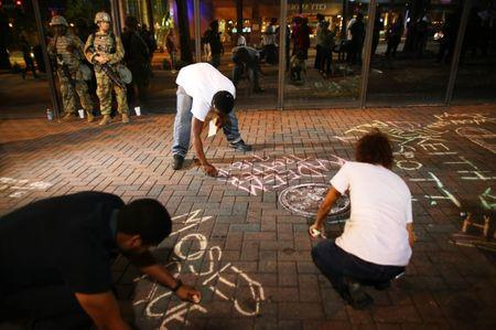 Protesters write the names of police shooting victims on the sidewalk while National Guard soldiers look on during another night of protests over the police shooting of Keith Scott in Charlotte, North Carolina, U.S. September 23, 2016.  REUTERS/Mike Blake