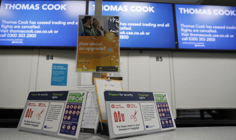 Empty Thomas Cook check-in desks are seen at Gatwick Airport, England, Monday, Sept. 23, 2019. Hundreds of thousands of travelers were stranded across the world Monday after British tour company Thomas Cook collapsed, immediately halting almost all its flights and hotel services and laying off all its employees.(AP Photo/Alastair Grant)