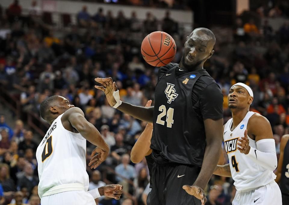 Central Florida's Tacko Fall (24) dodges a loose ball with VCU's De'Riante Jenkins and Corey Douglas (4) defending during the first half of a first-round game in the NCAA men's college basketball tournament Friday, March 22, 2019, in Columbia, S.C. (AP Photo/Richard Shiro)