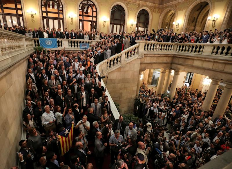 Catalan government members, pro-independence deputies and mayors from pro-independence towns sing the Catalan anthem after the regional parliament voted to declare independence.
