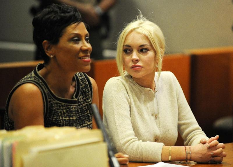 FILE - In this Dec. 14, 2011 file photo, Lindsay Lohan, right, alongside her attorney Shawn Chapman Holley appear during a progress report session at the Los Angeles Superior Court, in Los Angeles. A star of Disney films whose acting received early praise and attention, Lohan's 2007 two arrests for DUI and drug possession still haunts the actress today. While the 27-year-old has put those cases behind her, she remains on probation for a necklace theft case and lying to police about her role in a crash on Pacific Coast Highway. (AP Photo/Michael Nelson, Pool, File)