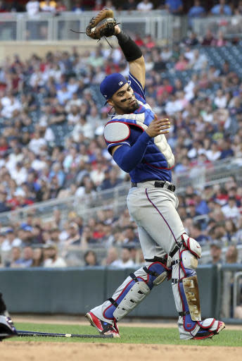 Texas Rangers catcher Robinson Chirinos catches a pop foul by Minnesota Twins' Brian Dozier for an out in the fourth inning of a baseball game Friday, June 22, 2018, in Minneapolis. (AP Photo/Jim Mone)