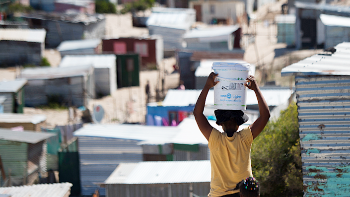 A woman carrying a bucket of fresh water to an informal settlement in Khayelitsha, near Cape Town- 31 March 2020