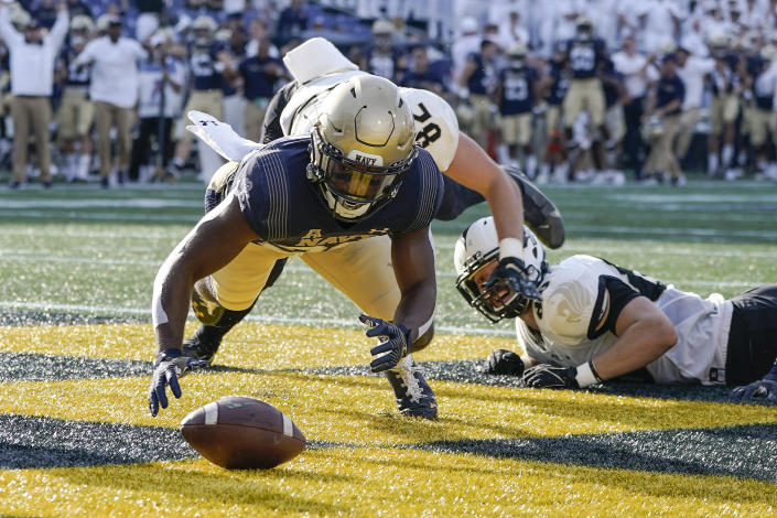 Navy's Daniel Taylor falls on the football in the end zone to score a touchdown on a blocked punt during the first half of an NCAA college football game against UCF, Saturday, Oct. 2, 2021, in Annapolis, Md. (AP Photo/Julio Cortez)