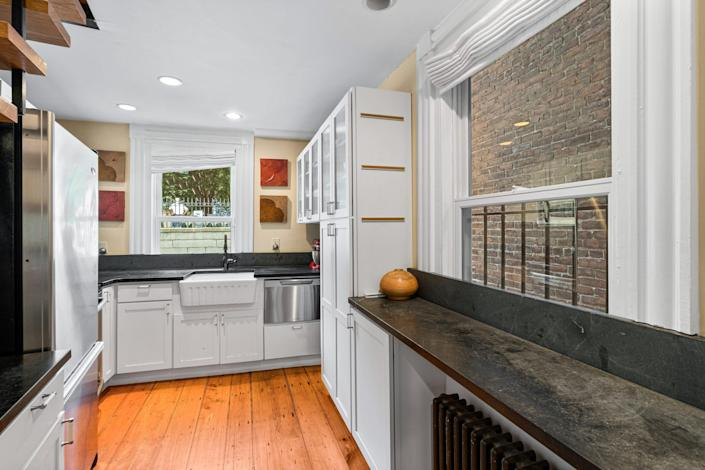 A narrow kitchen with wood floors, white cabinetry, and dark counter tops.