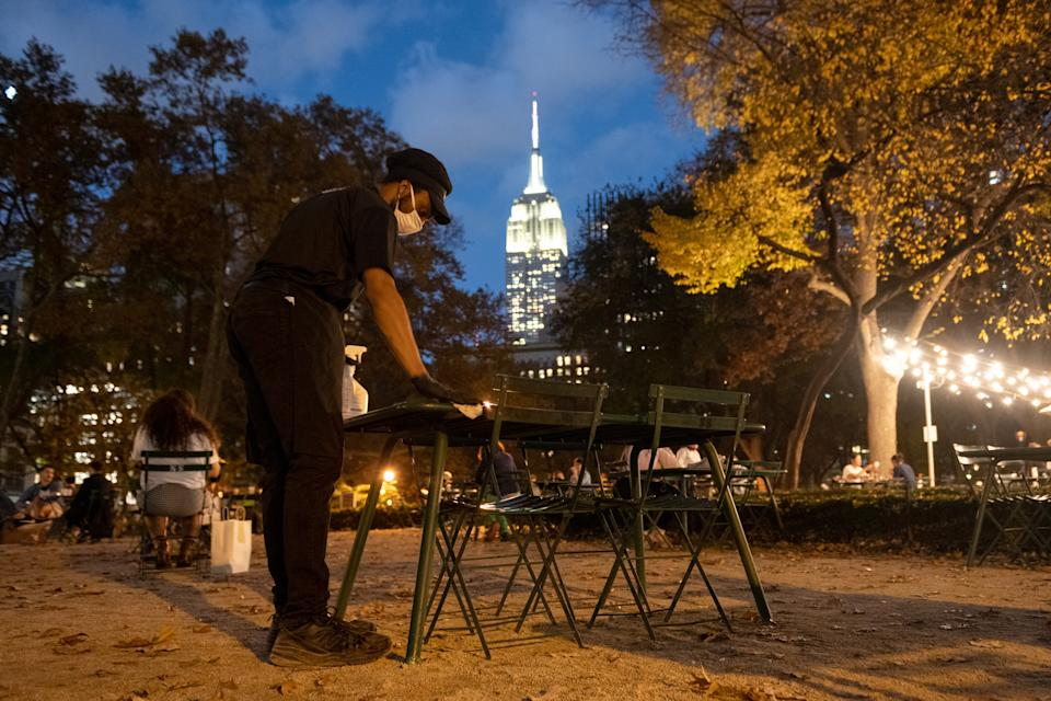 NEW YORK, NEW YORK - NOVEMBER 10: A shake Shack employee cleans and sanitizes an outdoor table at Madison Square Park on November 10, 2020 in New York City. The pandemic continues to burden restaurants and bars as businesses struggle to thrive with evolving government restrictions and social distancing plans which impact keeping businesses open yet challenge profitability. (Photo by Alexi Rosenfeld/Getty Images)