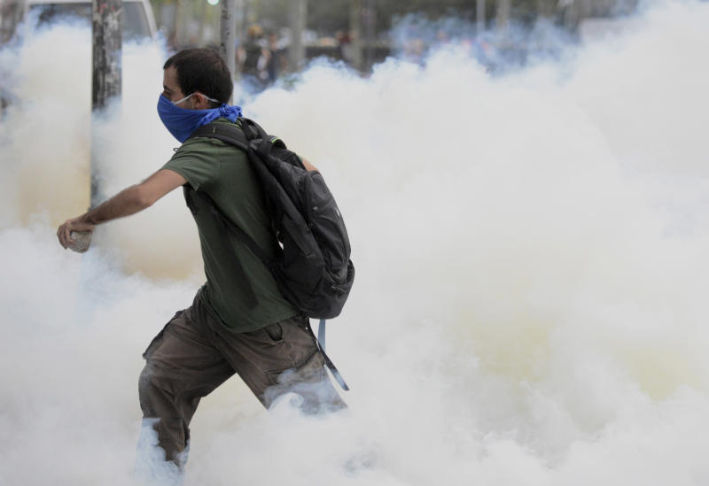 A man runs through smoke of tear gas fired up by riot police in Istanbul, Turkey, Friday, May 31, 2013. Riot police used tear gas and pressurized water to quash a peaceful demonstration by hundreds of people staging a sit-in to try to prevent the demolition of trees at an Istanbul park. (AP Photo)