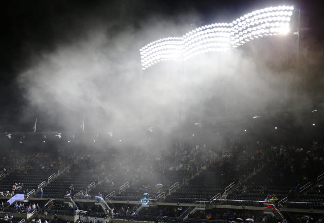 Fans watch the Miami Marlins play the New York Mets in the rain during the eighth inning of a baseball game Saturday, May 11, 2019, in New York. The Mets won 4-1. (AP Photo/Frank Franklin II)