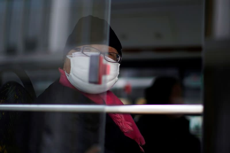 A man wearing a mask is seen on a bus, in downtown Shanghai
