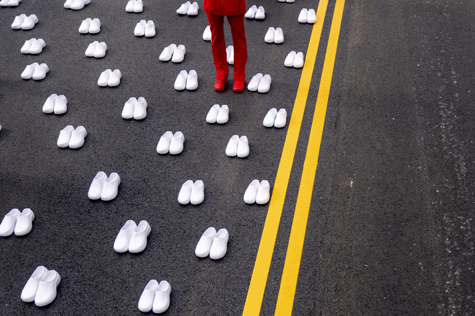 A woman in a nurses uniform stands surrounded by white pairs of shoes to represent the 402 nurses who died because of COVID-19, near the White House in Washington, Wednesday, May 12, 2021. National Nurses United union is asking the Biden administration to adopt Emergency Temporary Standards, which will require employers to continue to protect workers from COVID-19. (AP Photo/Andrew Harnik)