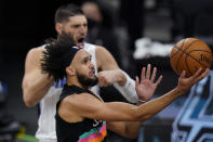 San Antonio Spurs guard Derrick White (4) drives past Orlando Magic center Nikola Vucevic (9) during the first half of an NBA basketball game in San Antonio, Friday, March 12, 2021. (AP Photo/Eric Gay)