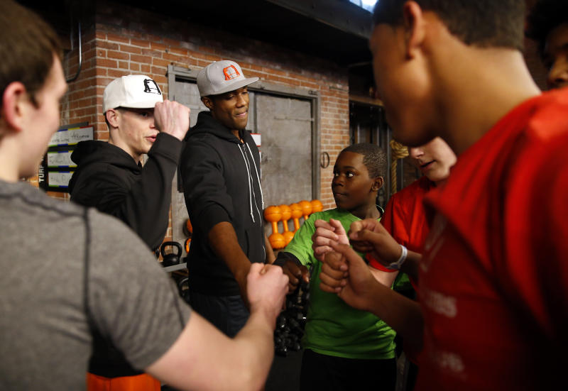 BOSTON - MARCH 22: Boys & Girls Clubs of Greater Boston members huddle with George Foreman III, center, and boxing trainer Shane Jordan, 21, of Brockton, Mass., after a work out session led by Jordan inside the high-end gym The Club By George Foreman III in the South Boston neighborhood on March 22, 2015. (Photo by Jessica Rinaldi/The Boston Globe via Getty Images)