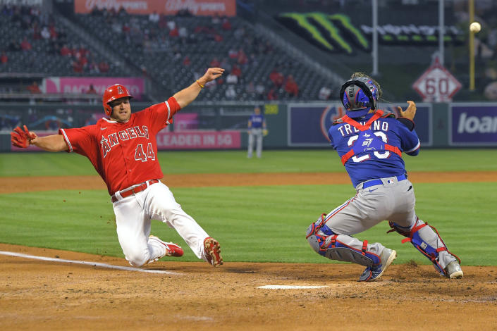 Los Angeles Angels' Scott Schebler, left, scores on a sacrifice fly hit by David Fletcher as Texas Rangers catcher Jose Trevino takes a late throw during the third inning of a baseball game Tuesday, April 20, 2021, in Anaheim, Calif. (AP Photo/Mark J. Terrill)