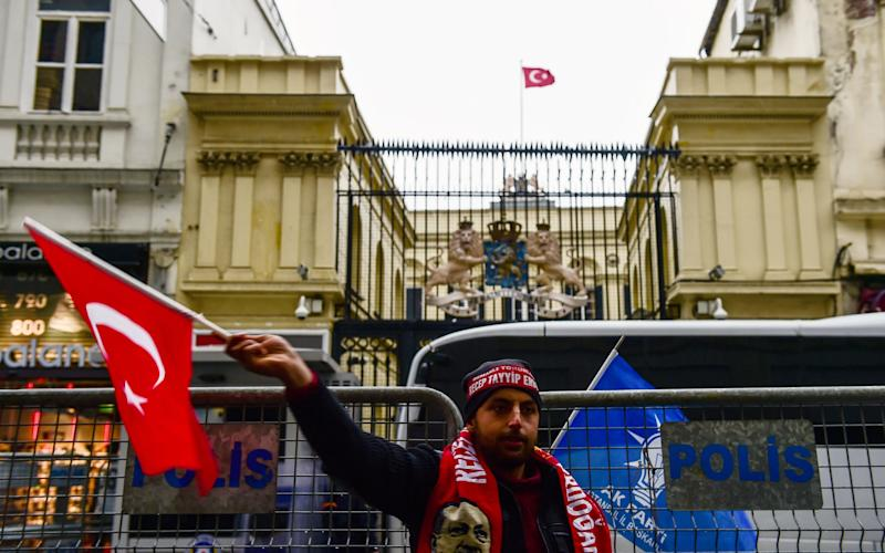 A man waves a Turkish flag in front of the Dutch Consulate where protesters have briefly replaced the Netherlands' national flag with a Turkish one - AFP or licensors