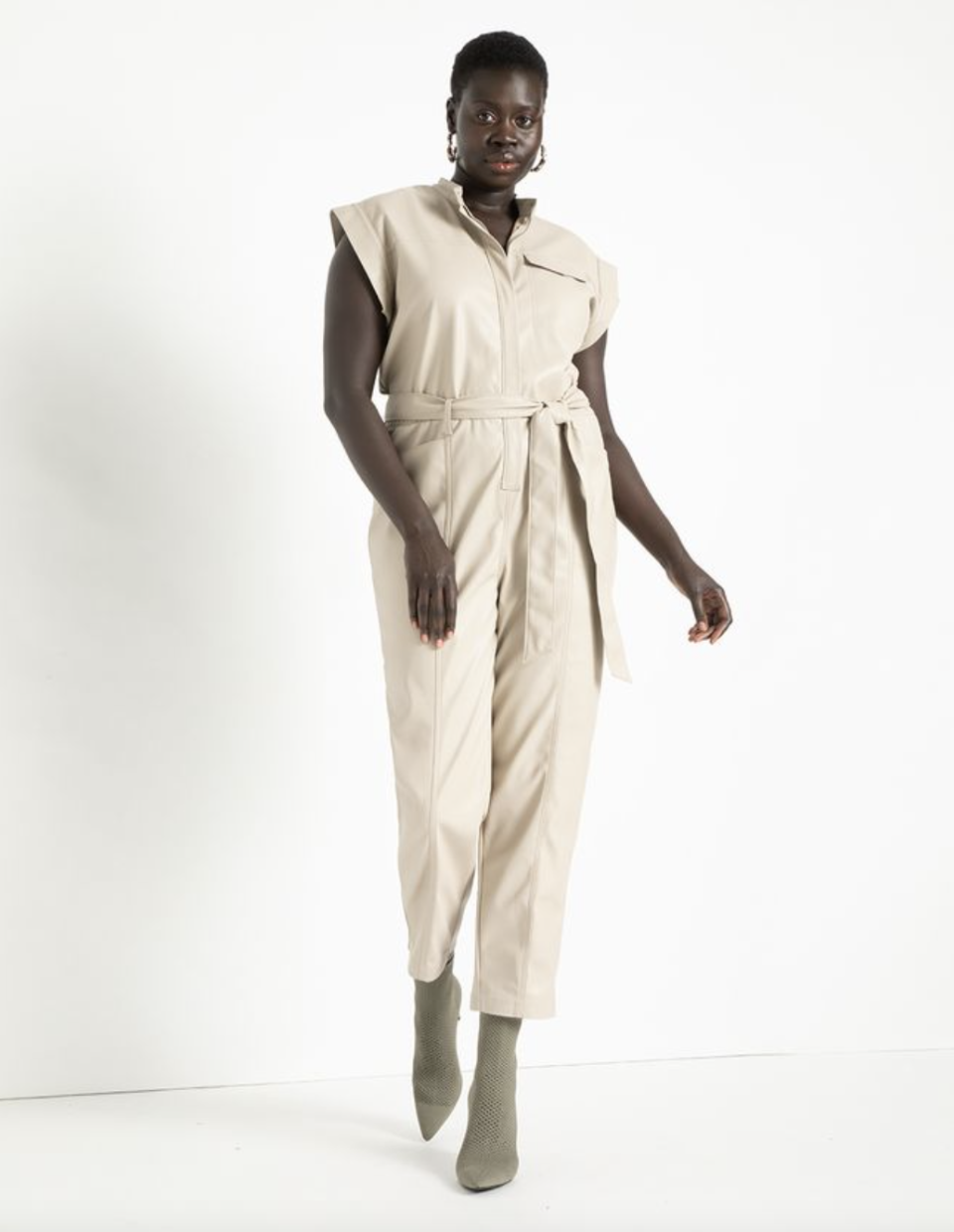black model with short hair posing in cream coloured faux leather jumpsuit and booties