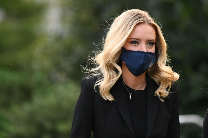 FILE PHOTO: White House Press Secretary Kayleigh McEnany wears a mask as she walks to a TV interview at the White House in Washington