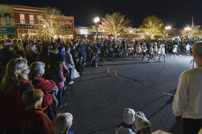A crowd watches a performance Friday, Dec. 11, 2020, during Christmas in a Railroad Town festivities in downtown Opelika, Ala. Doctors and nurses caring for the sickest COVID-19 patients are doing what they can to get through the holidays while neighbors and friends indulge in Christmas parades and tree lightings. (AP Photo/Julie Bennett)