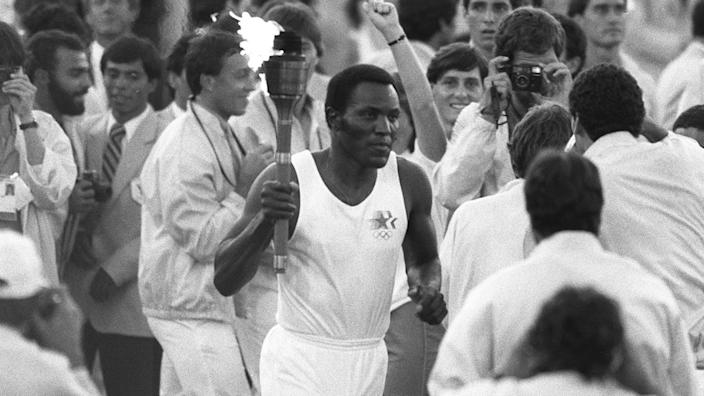 Rafer Johnson runs around the track at the Coliseum before lighting the Olympic flame on July 28, 1984.