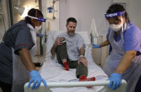Felicia Kwaku, Associate Director of Nursing, left, and Anna Castellano, Matron, right, help recovering COVID-19 patient Justin Fleming out of bed to try to walk again on the Cotton ward at King's College Hospital in London, Wednesday, Jan. 27, 2021. Fleming is one of more than 37,000 coronavirus patients being treated now in Britain's hospitals, almost double the number of the spring surge. King's College Hospital, which sits in a diverse, densely populated area of south London, had almost 800 COVID-19 patients earlier this winter. (AP Photo/Kirsty Wigglesworth, Pool)