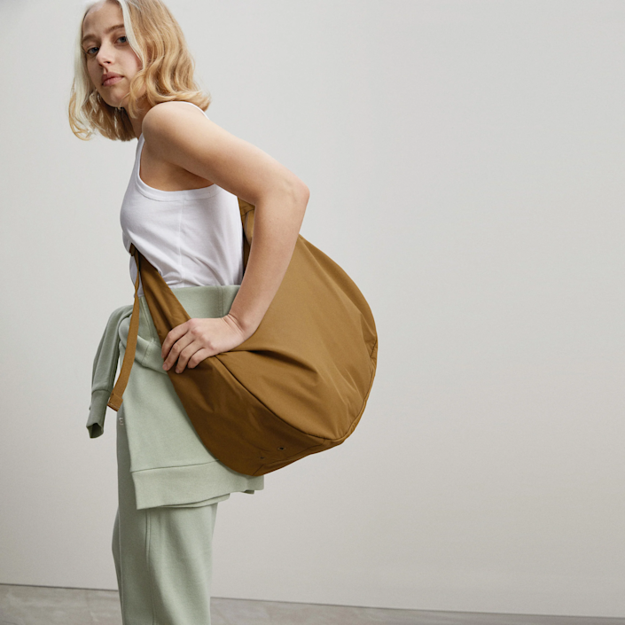 """<h2>Everlane The Oversized Carryall</h2><br>For a compact option, check out this oversized crossbody that is both machine-washable and roomy enough to fit everything you'd need for an overnight stay. <br><br><em>Shop <strong><a href=""""https://www.everlane.com"""" rel=""""nofollow noopener"""" target=""""_blank"""" data-ylk=""""slk:Everlane"""" class=""""link rapid-noclick-resp"""">Everlane</a></strong></em><br><br><strong>Everlane</strong> The Oversized Carryall, $, available at <a href=""""https://go.skimresources.com/?id=30283X879131&url=https%3A%2F%2Fwww.everlane.com%2Fproducts%2Fwomens-renew-caryall-bag-breen"""" rel=""""nofollow noopener"""" target=""""_blank"""" data-ylk=""""slk:Everlane"""" class=""""link rapid-noclick-resp"""">Everlane</a>"""