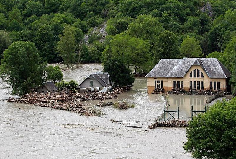 Buildings are surrounded by flood water near Lourdes, southwestern France, Wednesday, June 19, 2013. French rescue services and police are evacuating hundreds of pilgrims from hotels threatened by floodwaters from a rain-swollen river in the Roman Catholic shrine town of Lourdes. (AP Photo/Bob Edme)