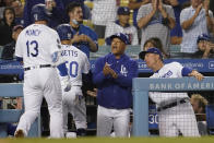 Los Angeles Dodgers' Max Muncy (13) and Mookie Betts are met at the dugout by manager Dave Roberts, center, and bench coach Bob Geren after Muncy's two-run home run during the third inning of the team's baseball game against the Arizona Diamondbacks on Tuesday, Sept. 14, 2021, in Los Angeles. (AP Photo/Marcio Jose Sanchez)